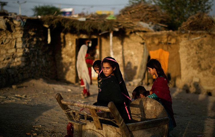 Refugee children mill around a cart as the sun begins its daily descent and casts a bronze hue on Islamabad, Pakistan, on June 30, 2012