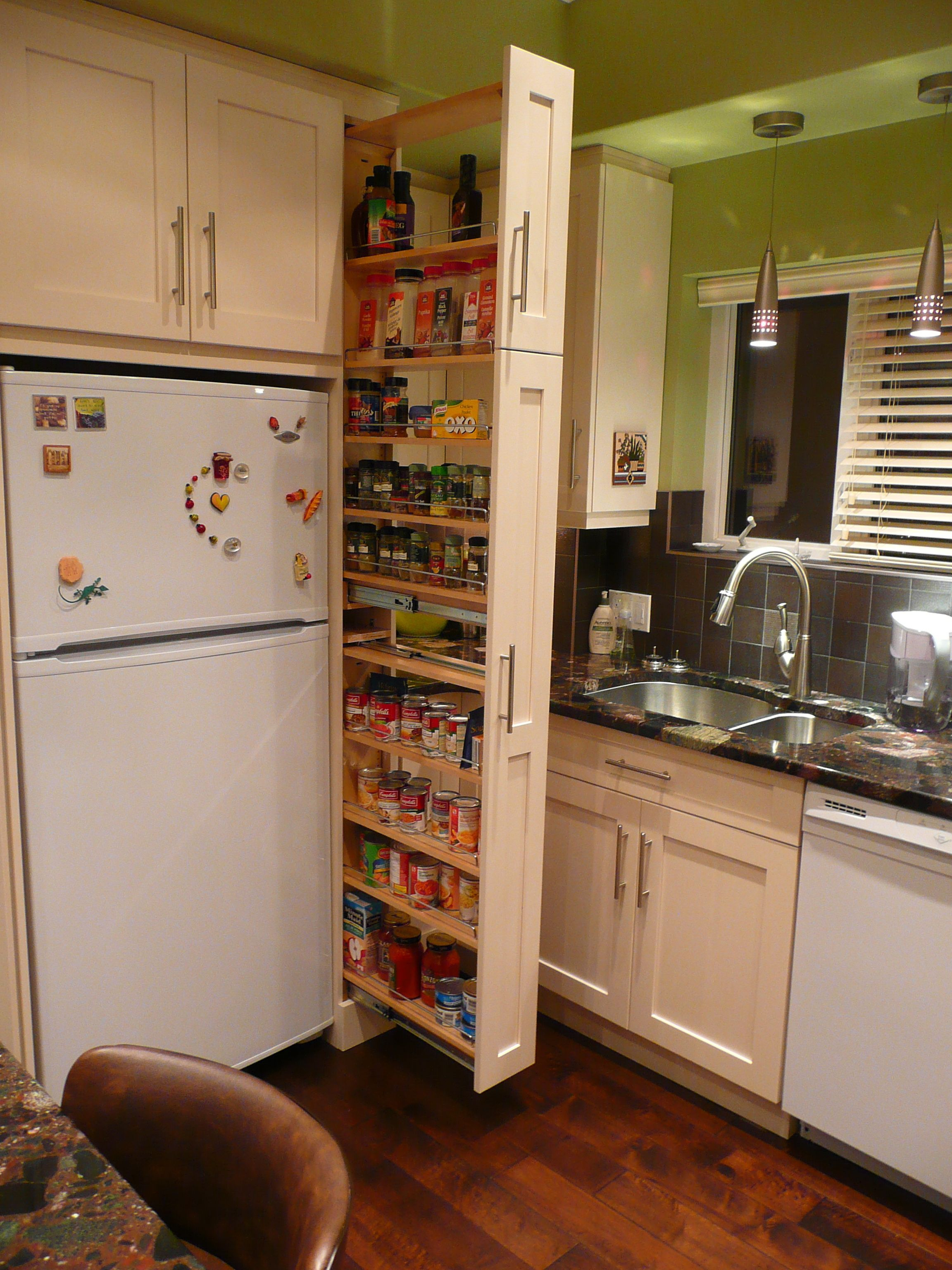 the narrow cabinet beside the fridge pulls out to reveal a spice canned goods pantry. beautiful ideas. Home Design Ideas