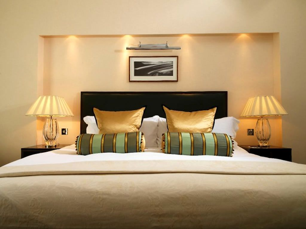 charming pillows interior design with gold color and desk lamps on majestic design resort hotel - Bedroom Hotel Design