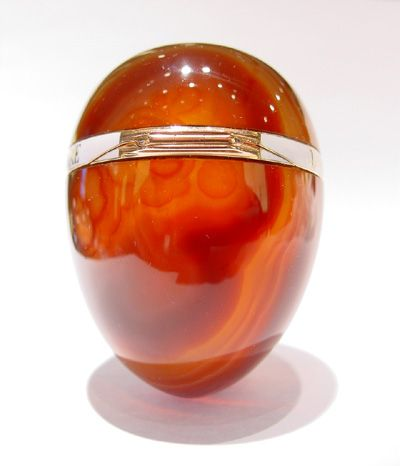An enamelled and gem set gold mounted agate bonbonniere egg by Carl Fabergé, the striated agate body with hinged gold mount enamelled opaque white and spelling in relief 'J'aime qu'on m'aime comme j'aime quand j'aime' (I like to be loved as I love when I love), with a demantoid garnet and rose diamond set pushpiece. Workmaster Michael Perchin, St. Petersburg, 1896-1903.