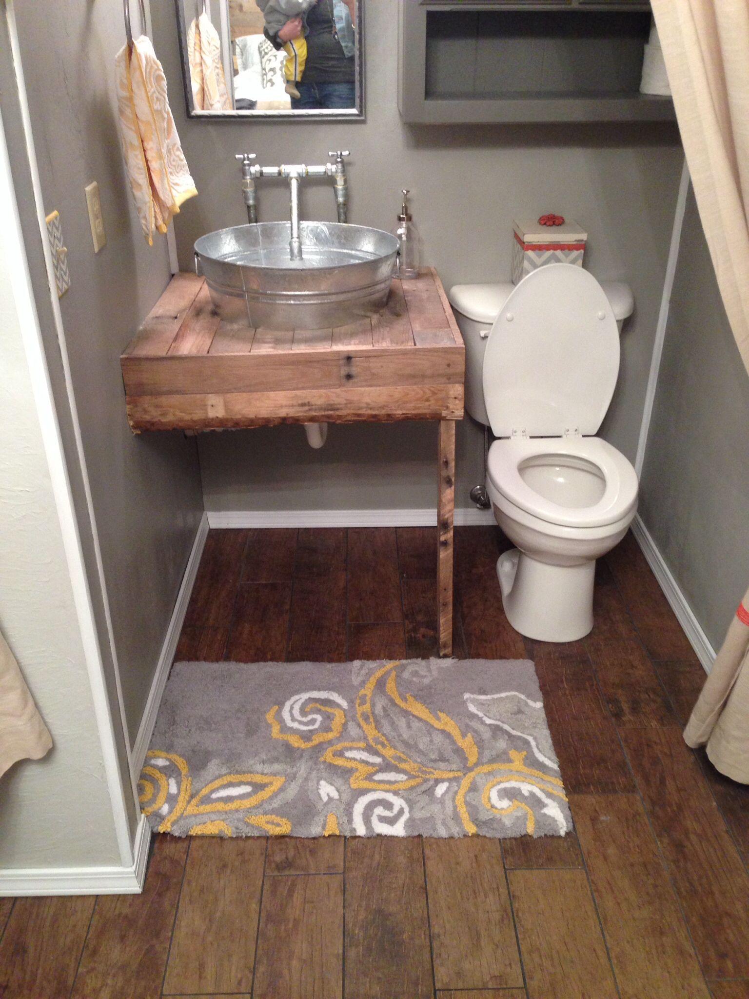 Porcelain plank floor. Pallet vanity. Galvanized sink and faucet.