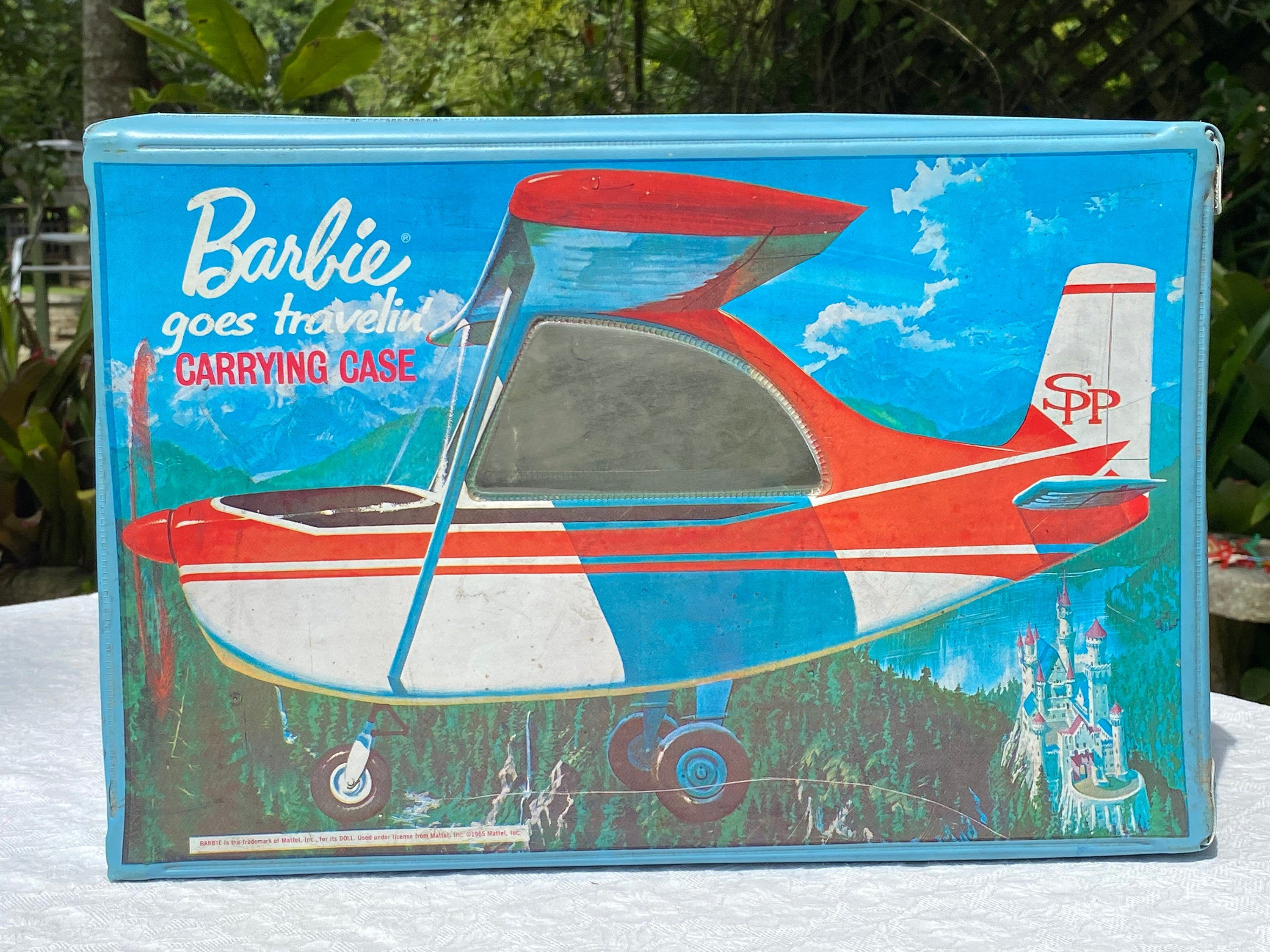 """""""This vintage Barbie Goes Traveling Carrying Case features an image of a biplane on one side and a car on the other. Each side has a clear plastic \""""window\"""" so that when Barbie is sitting inside the case it appears that she is looking out the window. This case was made in three colors - blue, yellow and salmon. This one is the blue version. It has a metal clasp (works well) and plastic handle. The inside features a seat, an overhead compartment and a hanging rack for clothes. Dates to the 1960s"""
