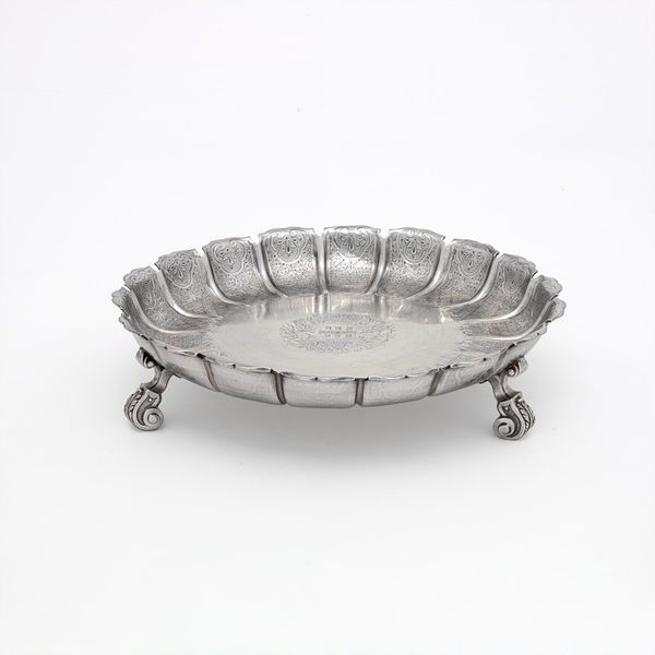 Strawberry  Dish 1720 Although not French, Nicolas Clausen was renowned for the Huguenot character of his work. The fine engraving and grandly cast feet, chased with foliage, are typical. This form of dish was at the height of fashion in the 1720s, but continued to appear until about 1750.