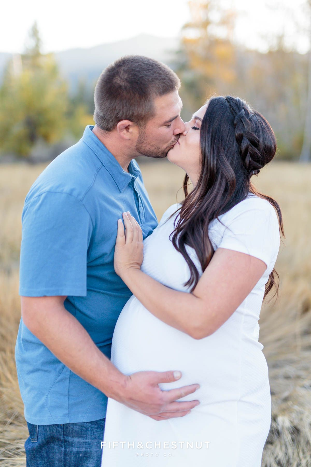 Husband And Wife Kiss For Their Fall Maternity Portraits By Reno Photographer In An Le Orchard Field With Mountains Behind Them
