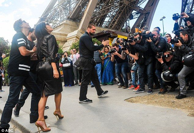 Awed: Kim Kardashian gazes up at the Eiffel Tower as she is surrounded by a group of snappers