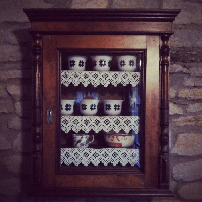 Rustic little cupboard with laced shelves for keeping antique porcelain
