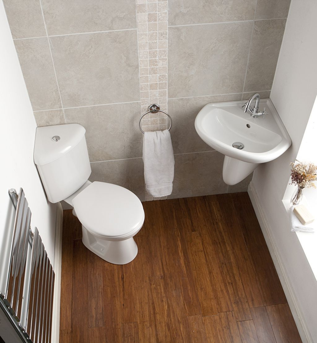 A Small Bathroom With Corner Toilet