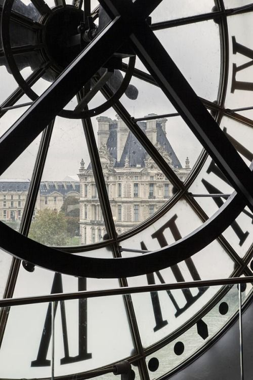 View through giant clock in Musée d'Orsay over Musée du Louvre, Paris France by Brian Jannsen