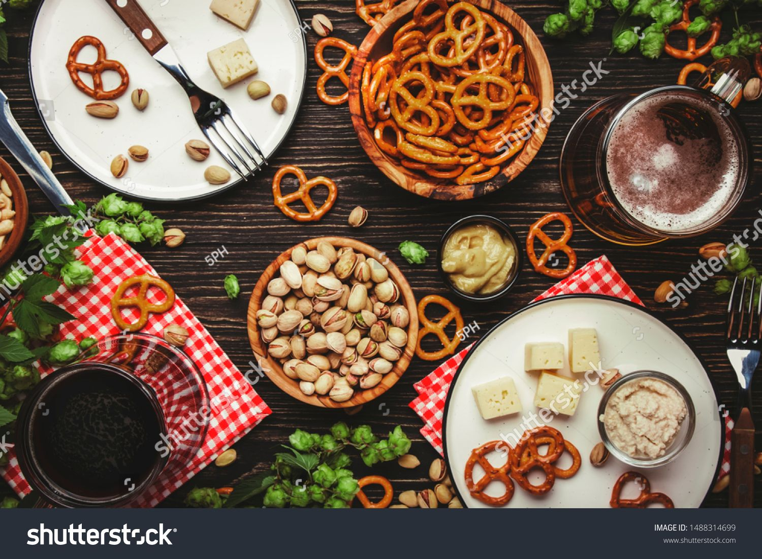 Light and dark beer in mugs and salty snacks and nuts dark wooden table frame with copy space top view