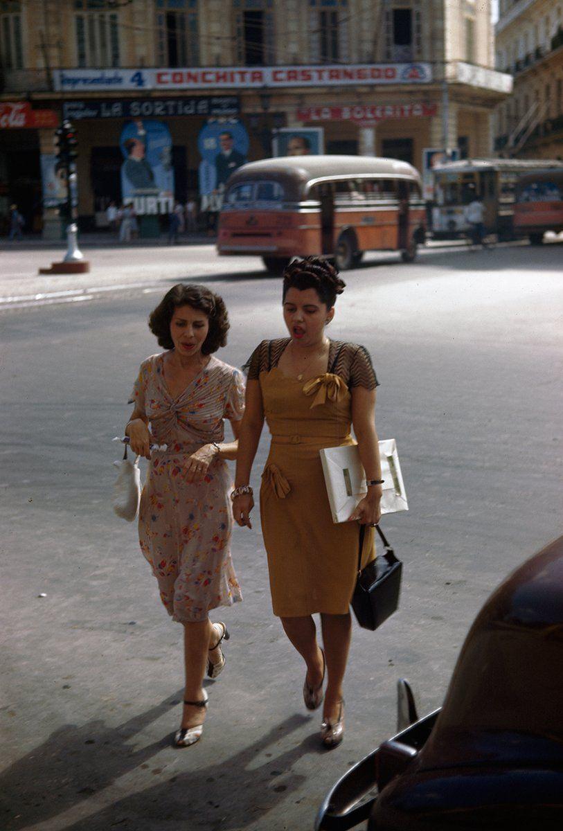 Two women on a shopping trip walk across a street in Havana, Cuba, 1947