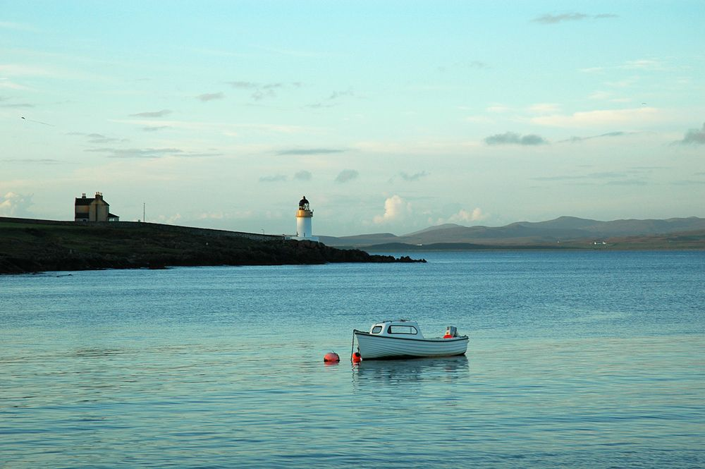 A beautiful evening on Islay with some mild light on Loch Indaal with the lighthouse near Port Charlotte. A kite flying in the evening sky.
