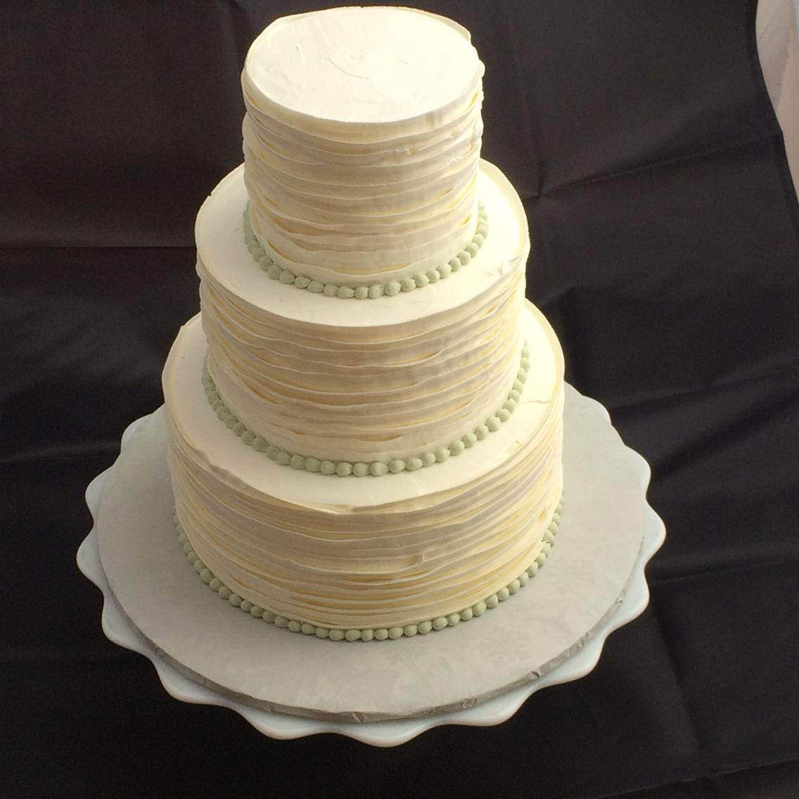 Small three tier wedding cake with texture ribbon in buttercream