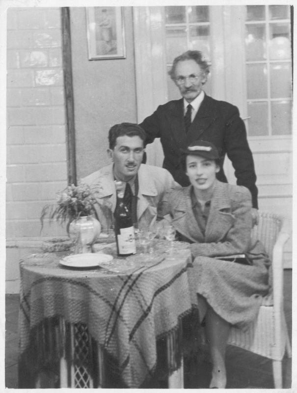 Three Polish Jews pose by a table set with wine and glasses.    Perec Willenberg is standing.  Seated are his daughter Itta and her fiancee Shmuel Kamrat. Kamrat immigrated to Israel. Itta remained in Poland, where she perished.