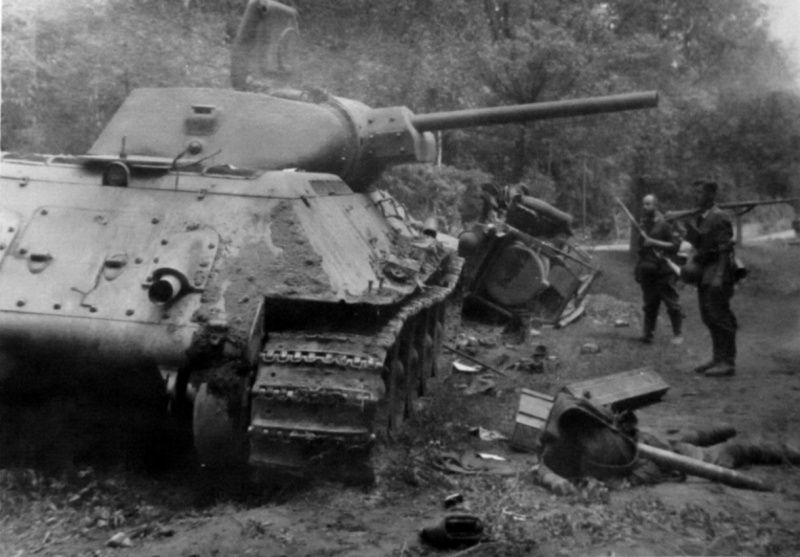 German soldiers next to a Soviet medium tank T-34. Near the dead body of a Red Army tanker