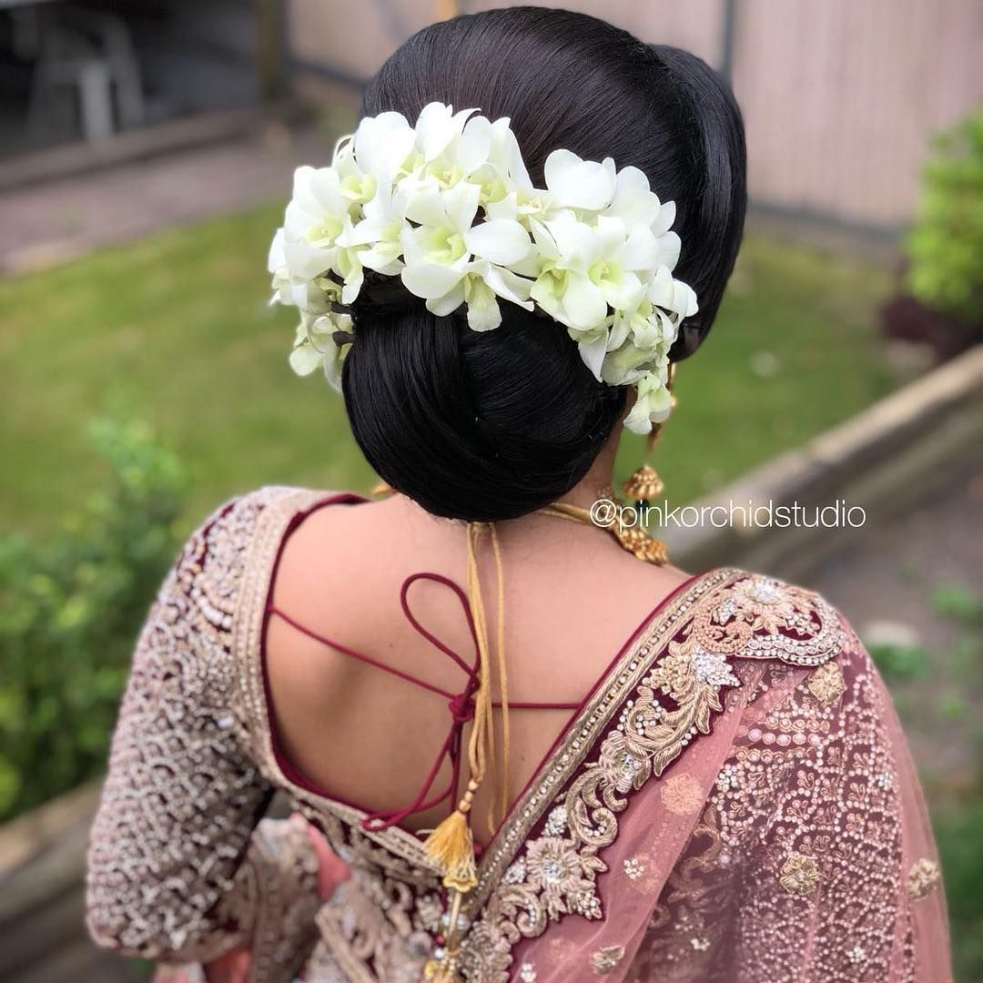 What A Beautiful Large Low Bun With Real Flower Gajra Care However Should Be Taken Before Adopting Such Hai Pink Orchid Studio Brunette Hair Color Bridal Updo