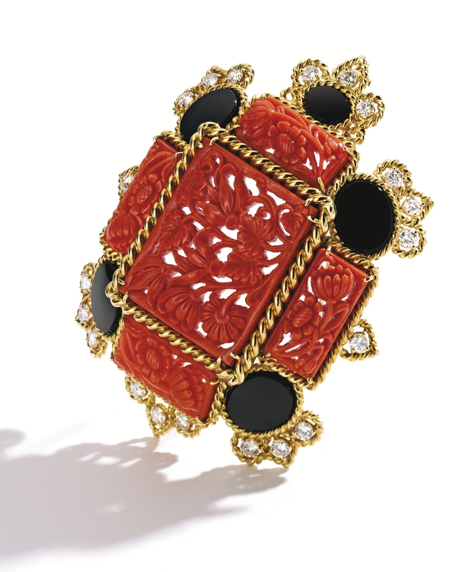 Suite of 18 Karat Gold, Coral, Onyx and Diamond Jewelry, Van Cleef & Arpels Comprising a necklace composed of coral plaques carved with floral motifs, spaced by onyx rings, set with round diamonds weighing approximately 2.25 carats, length 28 inches, numbered NY43220; pendant detachable, with brooch fitting; together with a pair of earclips of similar design, set with round diamonds weighing approximately 2.10 carats, signed Van Cleef & Arpels, numbered N.Y. 43316; pendants detachable; the…