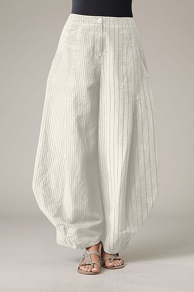 Trousers Santina. These extra-wide trousers are full of clever design details. At the hips two folds open and unique leg seams accentuate the forming volume. Classic: the zipper positioned at the middle with the overlying button. An elastic back waistband and two pockets are part of the typical OSKA look.