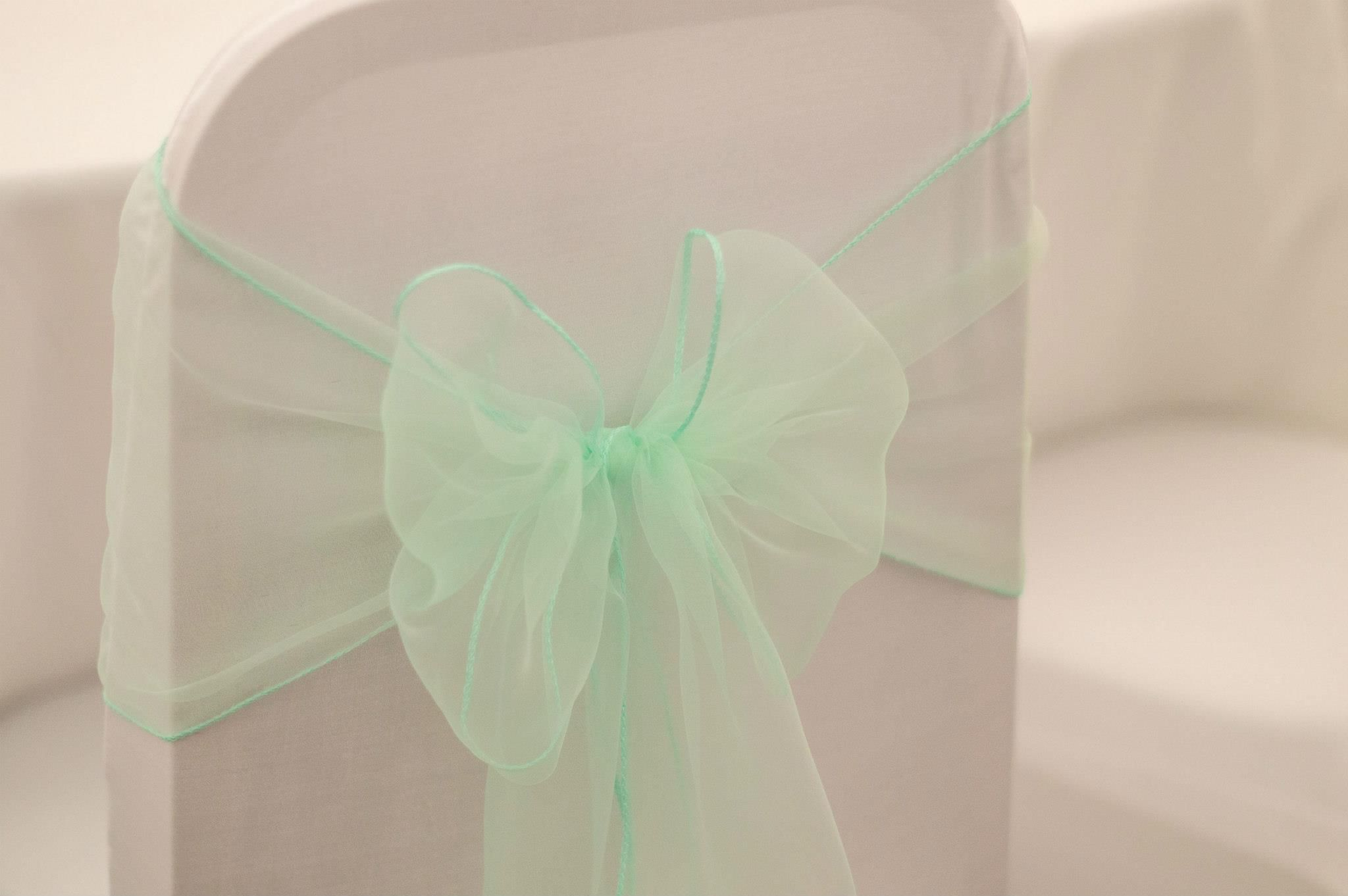 White chair cover with mint green organza chair sash