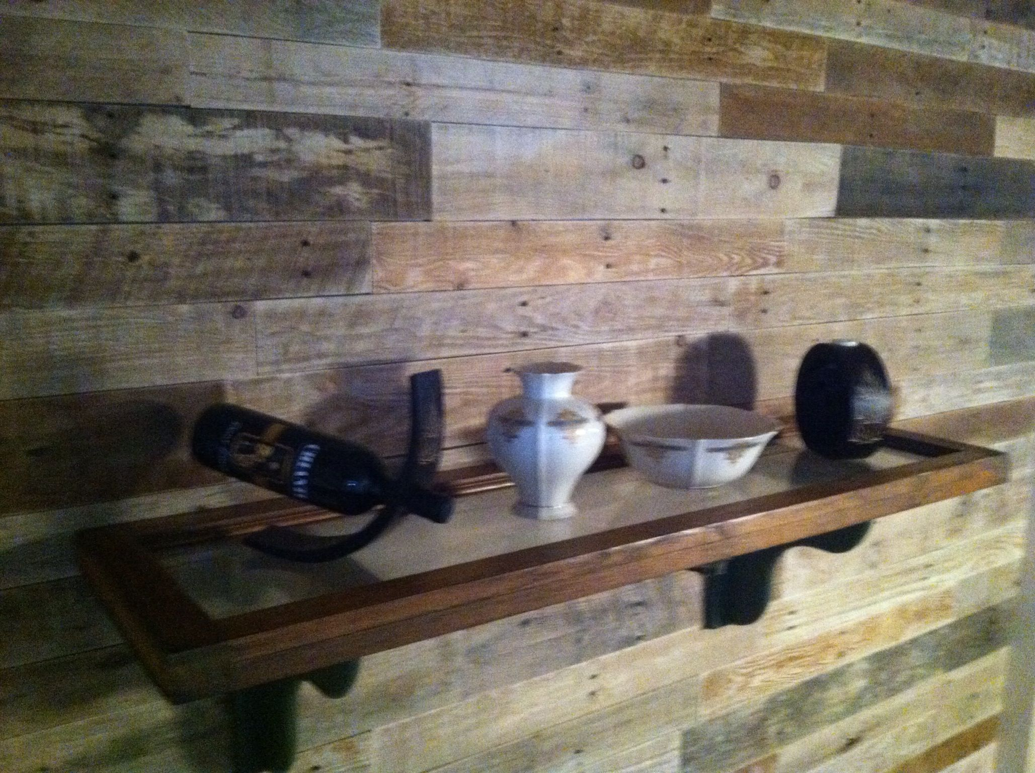 Wood Covered Walls mantle height shelf made from old transom window mounted on a wall