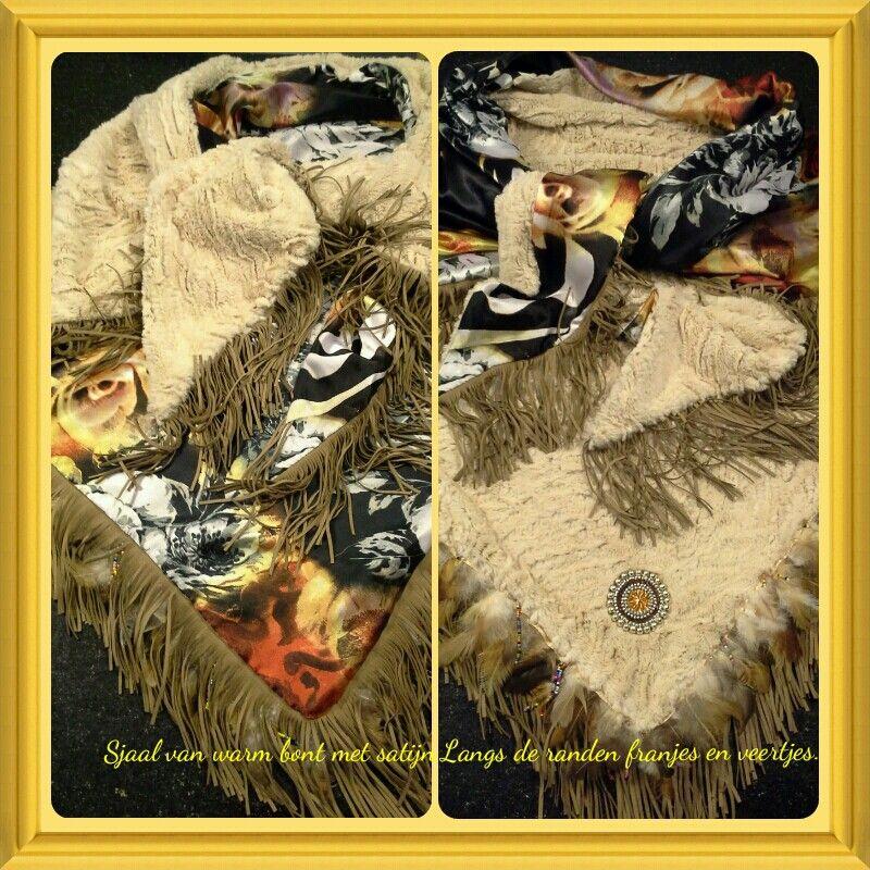 Sjaal van warm bont gevoerd met satijn. Afgewerkt met franje en veertjes band.