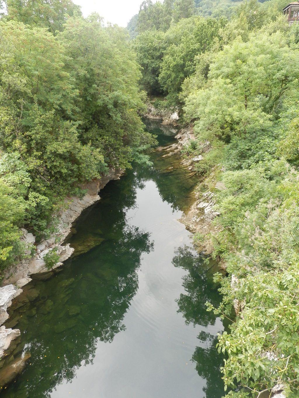 El río Pas de un tono oscuro cruza Puente Viesgo entre árboles erosionando una roca caliza blanca, dándole formas caprichosas