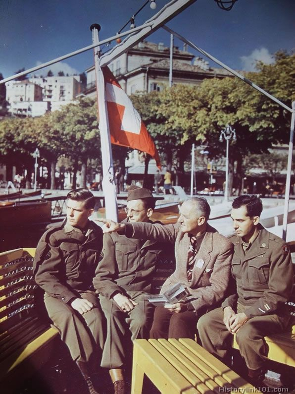 An English speaking guide explains points of interests on Lake Lugano to American soldiers touring in Switzerland, form the stern of a pleas...