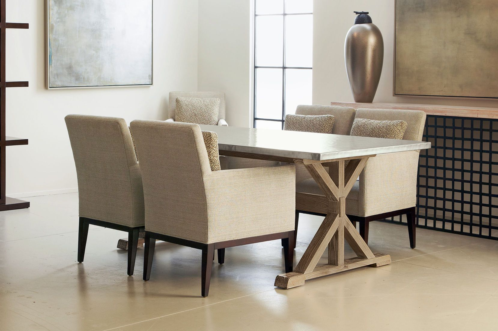 This beautiful dining room effortlessly combines wood legs and hammered metal surface with beautifully upholstered chairs.