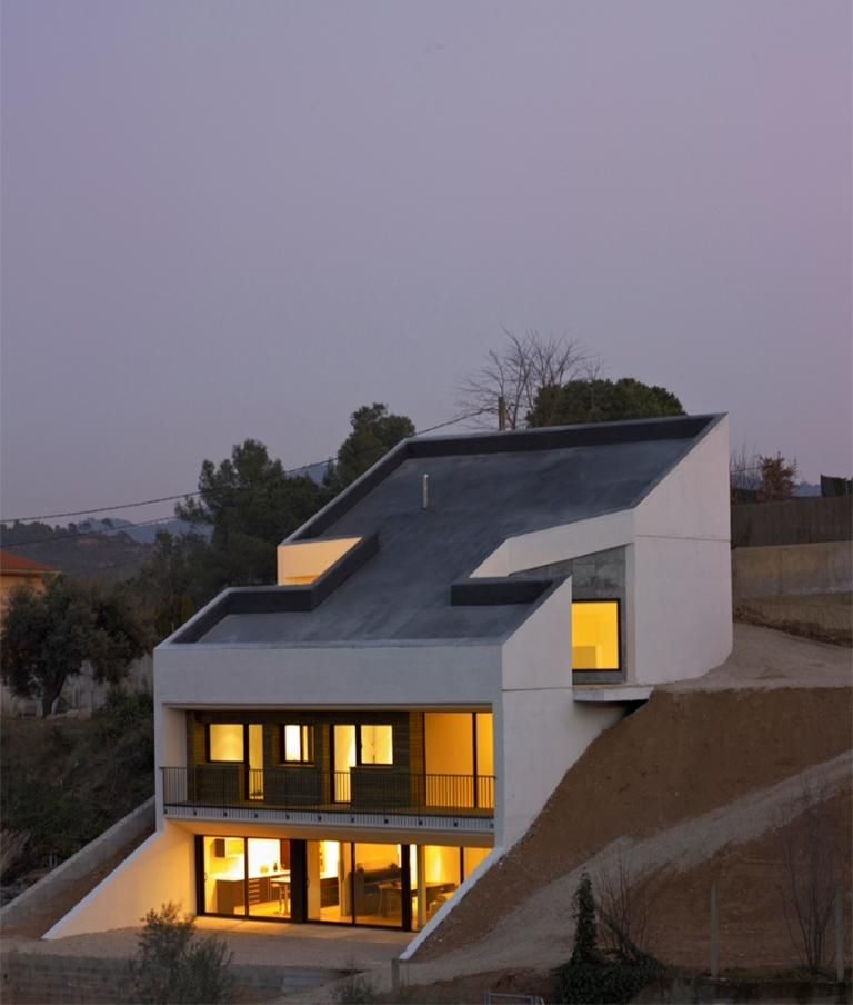 concrete house embedded in the slope architects house