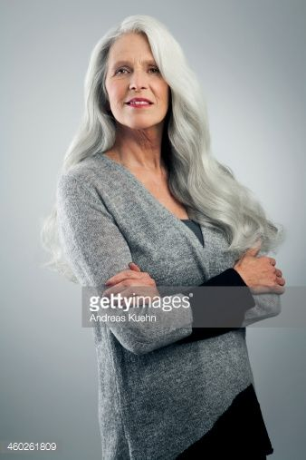 Mature woman in her sixties in front of gray background with long ...