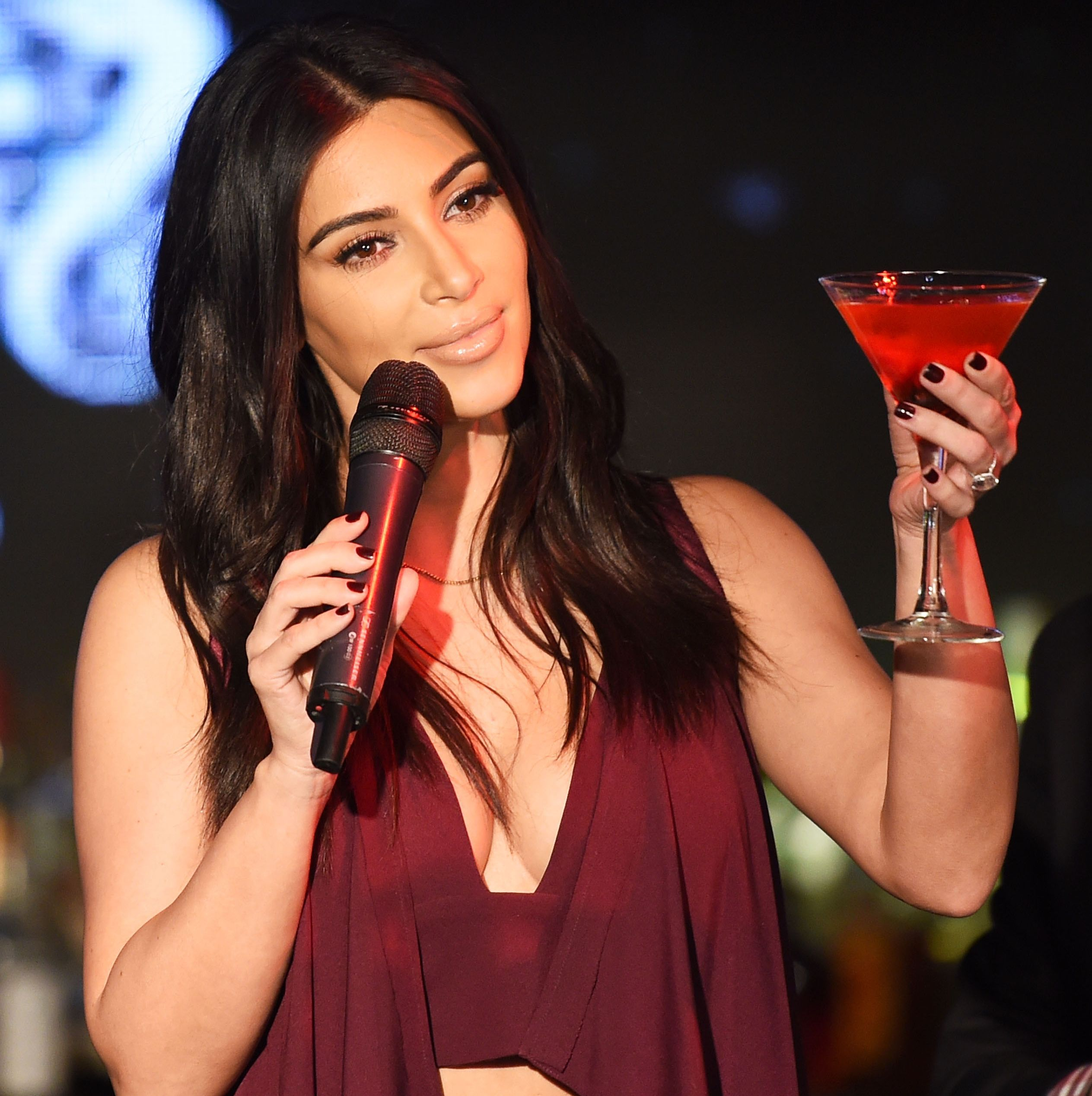 Kim Kardashian poses in orange as she promotes Sooo Fire