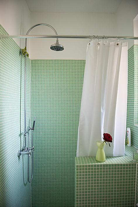 Schönes Badezimmer mit grünen Fliesen und weißem Duschvorhang ...