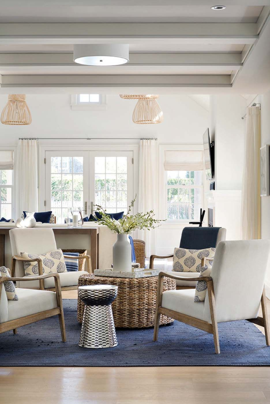 coastal beach living room with blue rug and white and ight wood ...