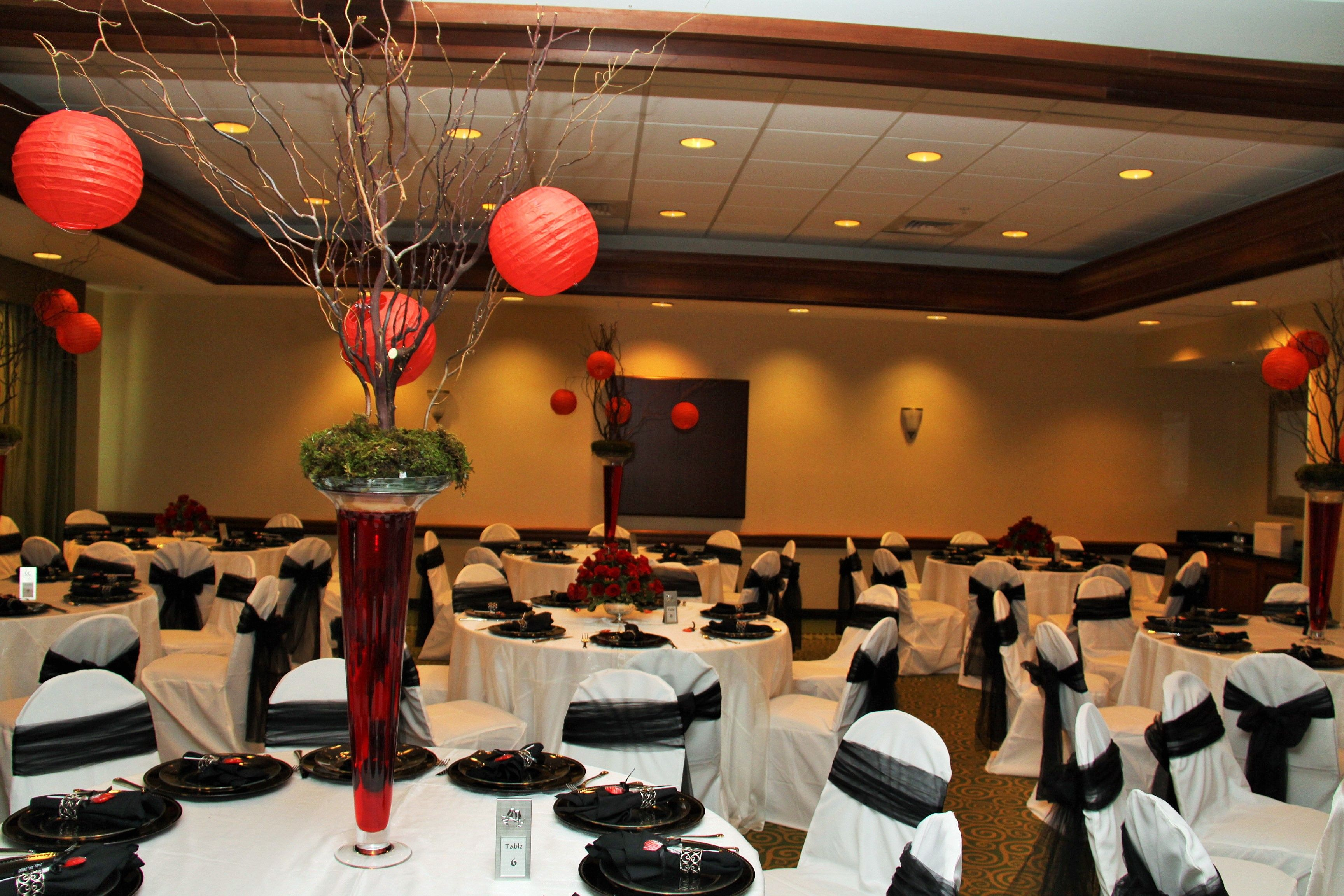 Wedding Decor- White Linen, White Chair Covers with Black Bows and Manzantia Tree Centerpiece with Red Hanging Lanterns