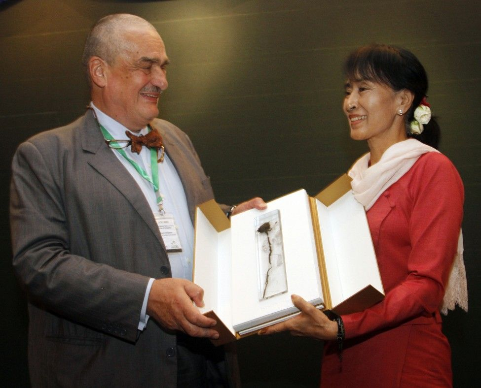 Burma's opposition leader Aung San Suu Kyi receives a posthumous gift from Foreign minister of Czech Republic Karel Schwarzenberg during their meeting at Thingaha hotel in Naypyitaw, Burma. (AP)