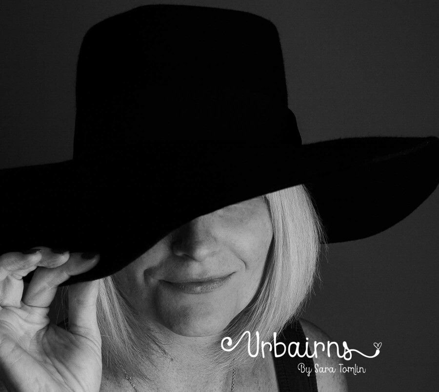 Black and white headshot with a hat