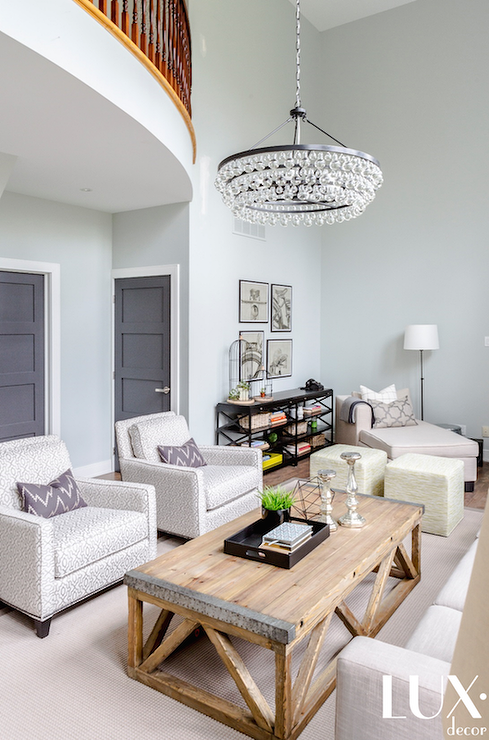 Two Story Living Room Features A Robert Abbey Bling Chandelier In Bronze  Over A Pair Of Gray Geometric Chairs Lined With Purple Lumbar Pillows  Situated ...