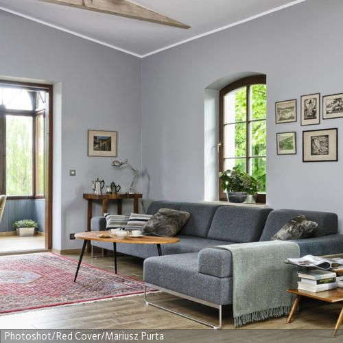 Die kühle Wandfarbe im geräumigen Wohnzimmer wird durch den