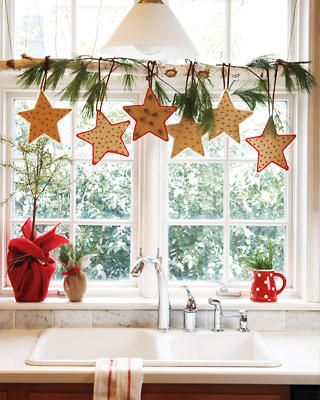 Light Sprays Of Greenery Combined With Hanging Star Cookie Ornaments Christmas Kitchen Window Display