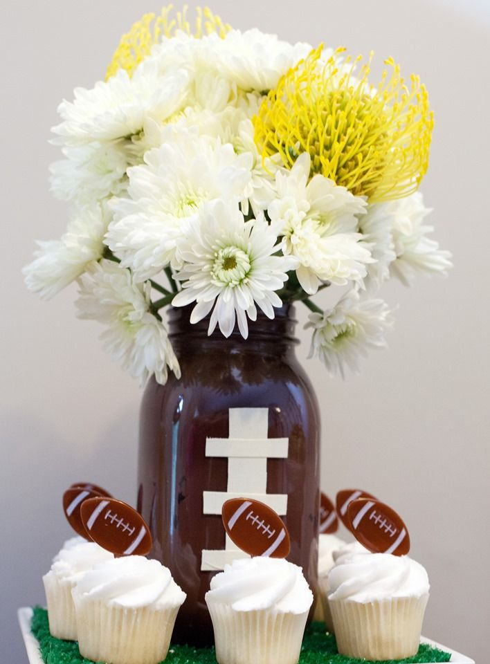 To inject more #SundayFunday spirit into your decor, get creative with your centerpiece! Grab a few empty mason jars and paint them brown (with white laces!) to give off the appearance of a football. Fill up the jars with seasonal flowers grouped together for your centerpiece. You can also swap painted mason jars for football-shaped koozies for the same look! #TailgatingTips  Credit to Kathryn Hastings Photography