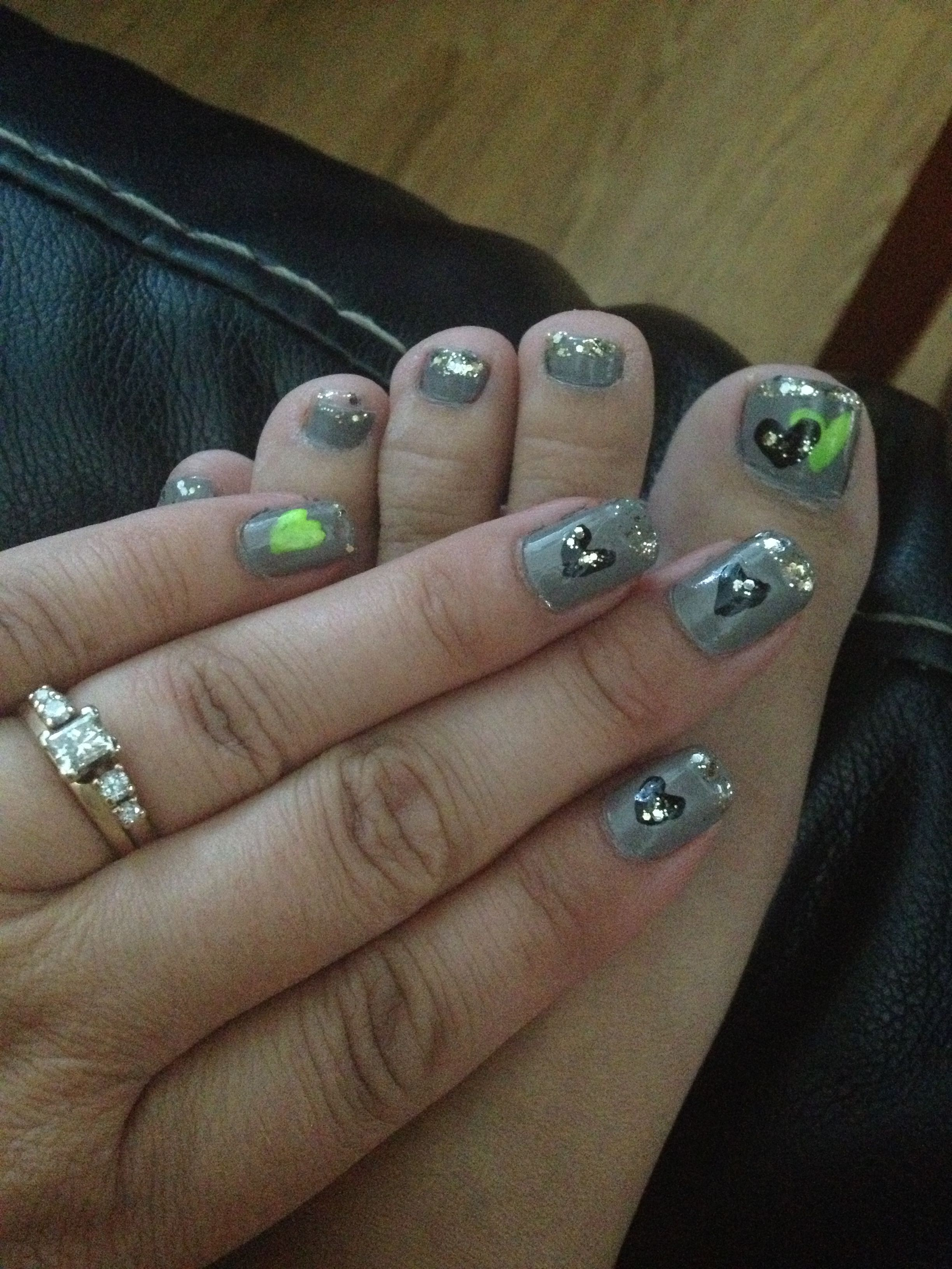 Gray nails with neon lime green hearts and black hearts tipped with gold glitter