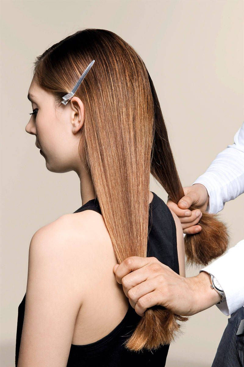 key to low knot is keeping sleek base; sectioning clips on each side will ensure front of hair remains smooth; create middle part at back, as you would for 2 low side ponytails