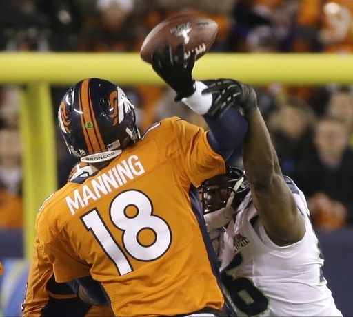 Denver Broncos' Peyton Manning is hit by Seattle Seahawks' Cliff Avril as he throws an interception during the first half of the NFL Super B...