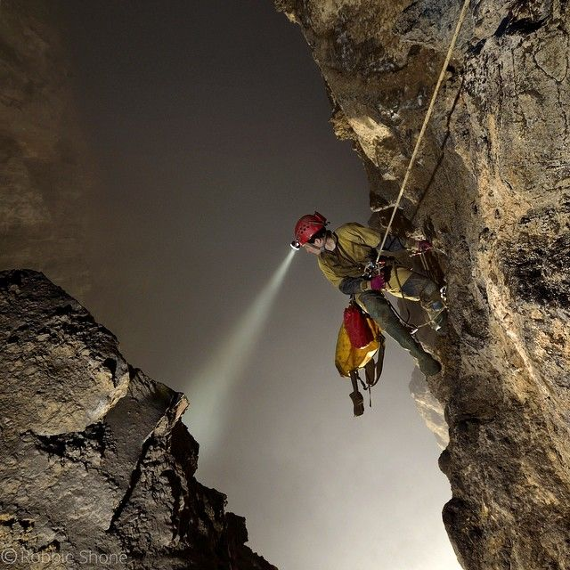 An American explorer peers down over her shoulder into Cloud Ladder Hall; one of the world's largest underground chambers. Although it can't be seen due to the dense fog that lingers around, the floor is over 250 metres (820 ft) below.