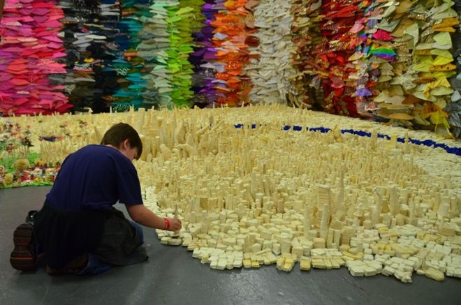 """The brainchild of artist Danny Scheible, Tapigami is an """"ever expanding, self generating social sculpture"""" made from common but carefully crafted masking tape.    Displeased with not being allowed to touch things at traditional galleries, he sought to make art that people to participate with. The incredible Tapigami tape city has formed over seven years of construction and events"""
