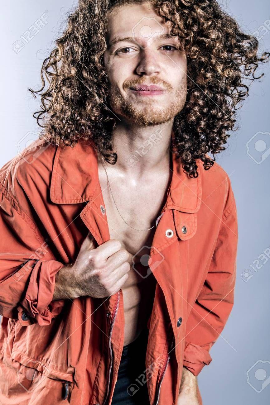 Attraktiver junger Mann mit langen Ingwer-Locken in Orange, Männer mit langen …