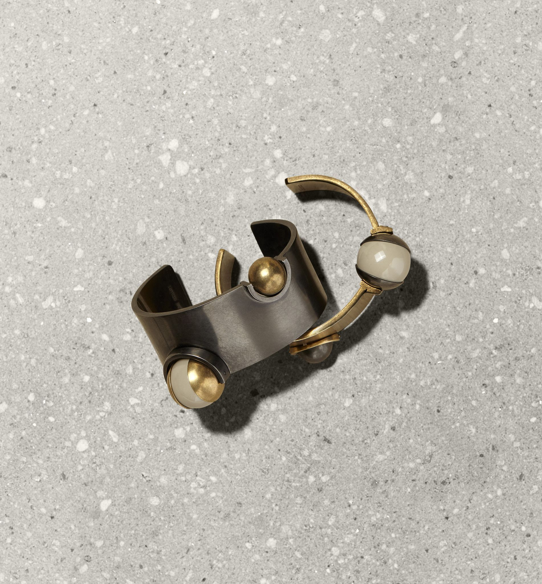 Dark brass cuff with rotating brass and lucite spheres #tomasmaier #jewelry