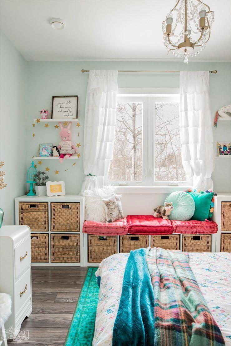 Kids boho inspired bedroom design with upcycled screen headboard, deep teal wall, star decals, IKEA window seat hack, and unicorn accessories #bedroomidea