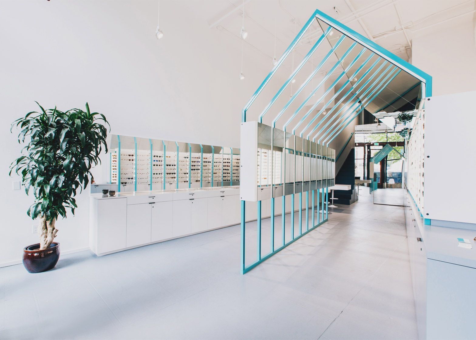 Eyeglasses are displayed within a steel-framed enclosure that resembles a house in this Seattle eyewear shop by local firm Best Practice Architecture.