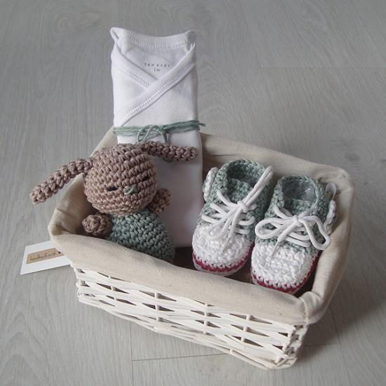 Fantástico regalo de nacimiento. Consta de una cestita de mimbre forrada con una telita cruda que contiene unos patucos de 0 a 8 meses (aprox.), un conejito y un body.