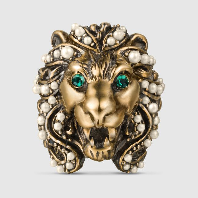 324ee7122af5d4 Gucci ring made in metal with a aged gold finish with a lion head design  adorned with crystal green eyes and glass pearls embedded in its mane.